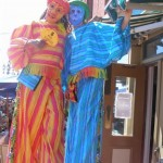 Two friendly masked stilt walkers in orange and blue striped outfits